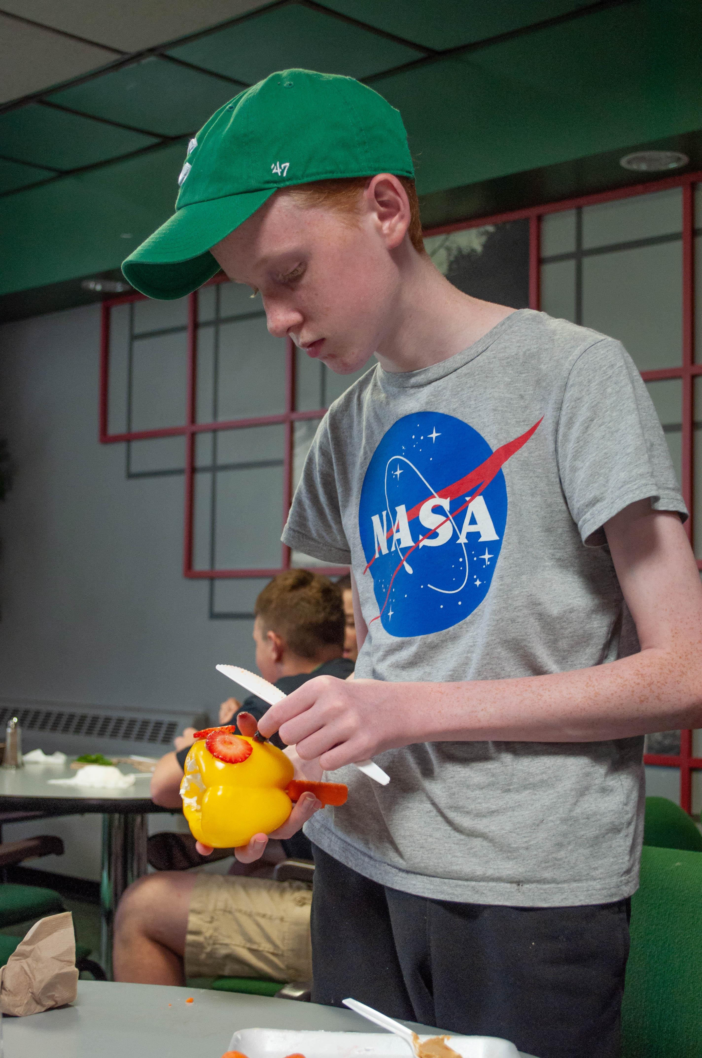 Child creating vegetable art
