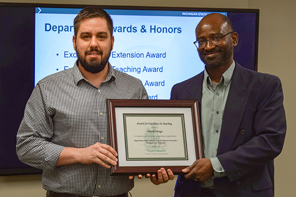Dr. David Ortega with AFRE Chair Titus Awokuse receiving his award
