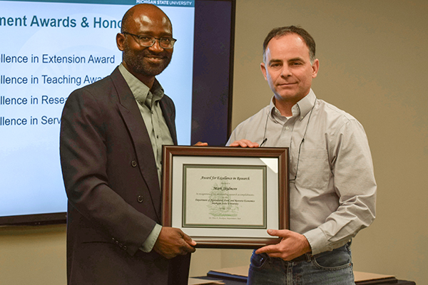 Dr. Mark Skidmore with AFRE Chair Titus Awokuse receiving his award