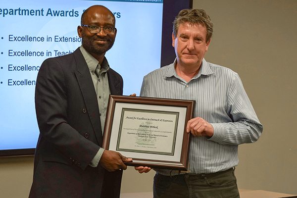 Matt Birbeck with AFRE Chair Titus Awokuse receiving his award