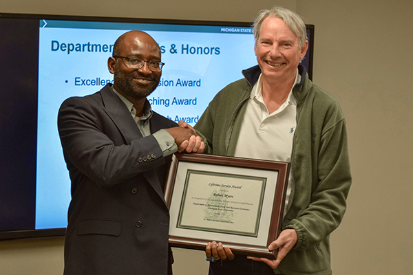 Dr. Bob Myers with AFRE Chair Titus Awokuse receiving his award