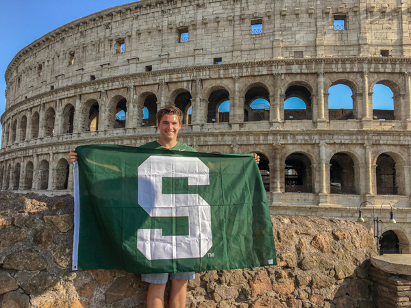 AFRE undergrad student holding Spartan flag in front of the Colosseum