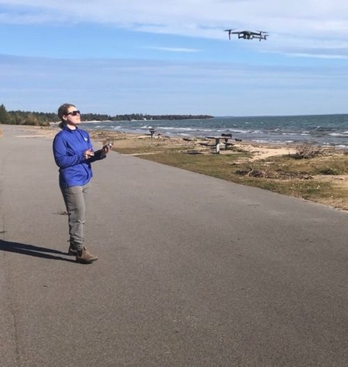 Woman stands near a lakeshore beach and holds drone controls in her hand as she lands the drone that can be seen in the air near her.