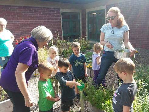 Students and Extension Master Gardeners examine a rain gauge