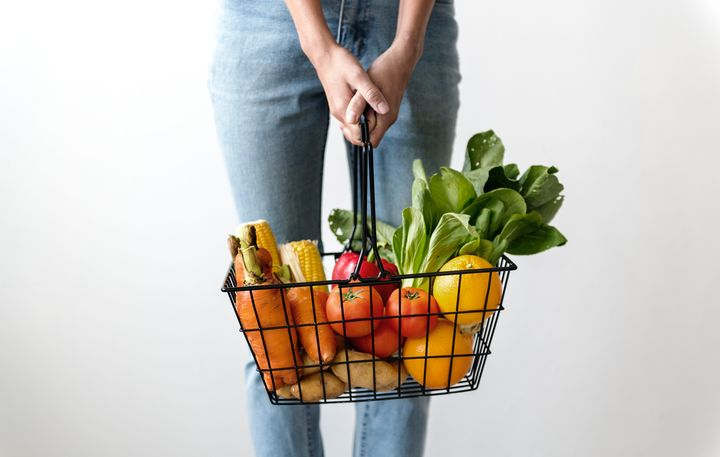 A grocery basket filled with carrots, corn, oranges, tomatoes and leafy greens.