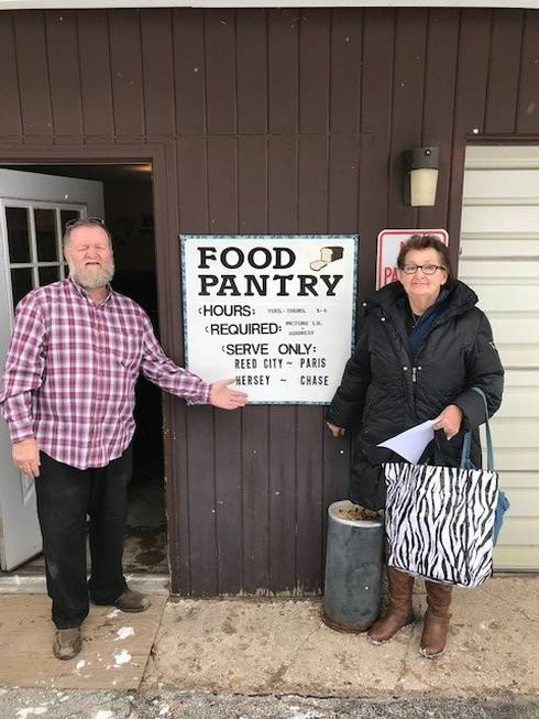 Burley Russell, director of the Reed City Food Pantry in Osceola County, poses with pantry client Sharon Lee-O'Brien.