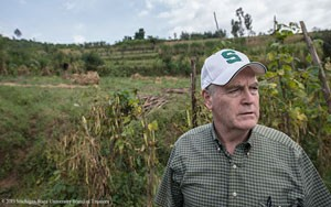 MSU AgBioResearch scientist Jim Kelly looks over a climbing bean test plot on a Rwandan farm. Photo courtesy of MSU.
