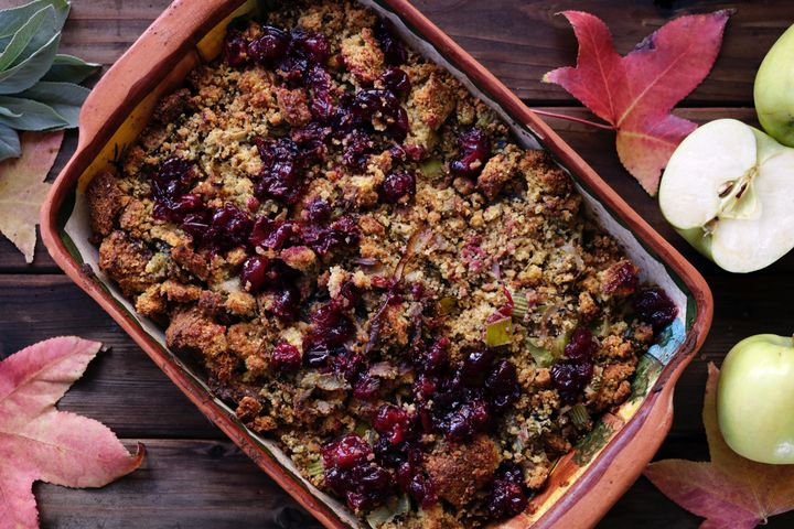 Stuffing in dish topped with cranberries.