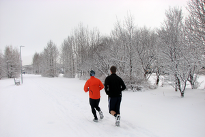 Two people running on a path in the snow.