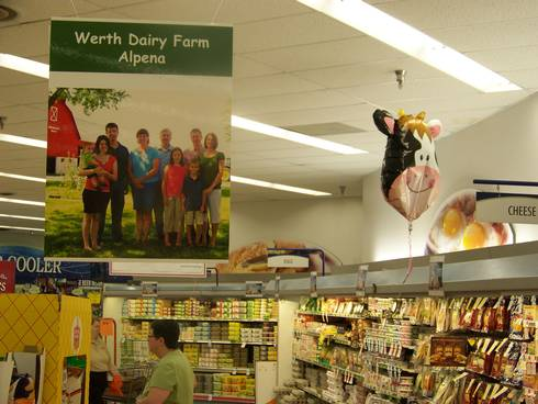 Werth Dairy Farm poster hanging in the dairy section of Neiman's Family Market in Alpena. The photo used to create this poster was provided by the United Dairy Industry of Michigan (UDIM).