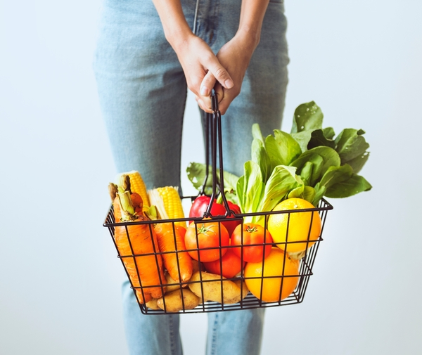 Woman holding basket of fresh vegetables.