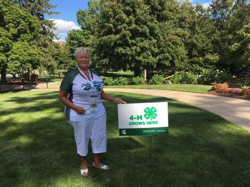 Pam Babbitt, Muskegon County 4-H volunteer and Michigan 4-H Foundation trustee in front of a 4-H Grows Here yard sign.