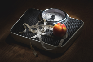 Bathroom scale with cloth tape and apple on top.