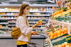 A woman look at fruit in the produce section of a grocery store.