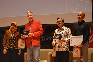 Image of Jon Burley and other speakers receiving presentation awards.