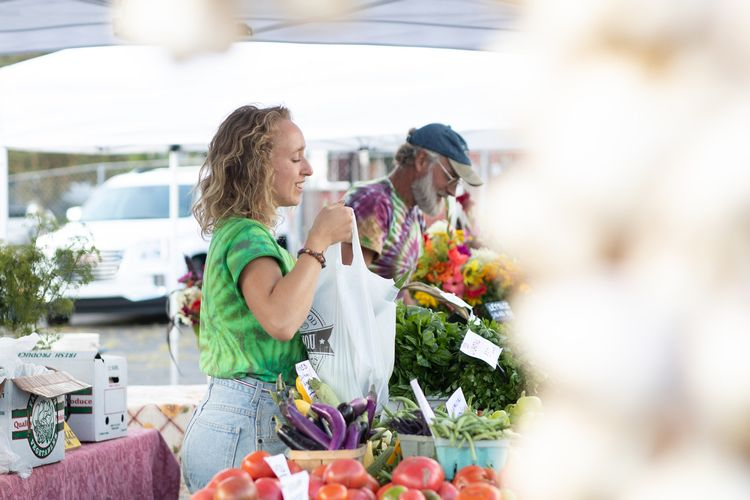 Woman hands a bag of produce over the stall at a farmers market
