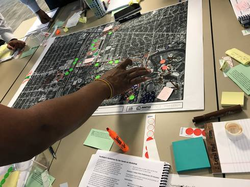 Hand placing dots on a neighborhood plan during group work at an NCI charrette training session.