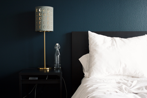 A bed pushed up against a blue wall with a lamp and glass of water on the night stand.