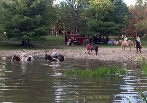 Horseback riders going into water
