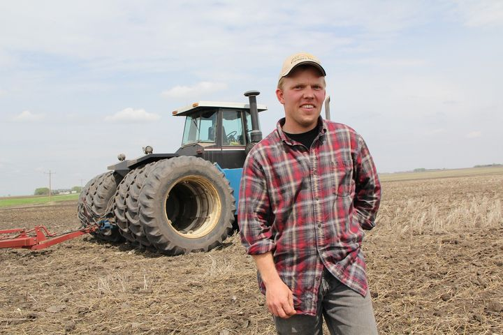 A man standing in front of a tractor in a field.