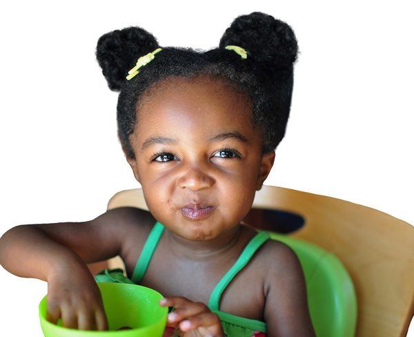 A young girl is eating food from a bowl.