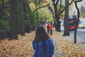 Girl with backpack on walking on sidewalk covered in leaves.