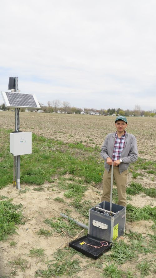 Ehsan Ghane stands with a controlled drainage structure in Elkton, MI. Photo credit: Anonymous