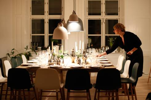 Woman in black dress setting table for holiday dinner.