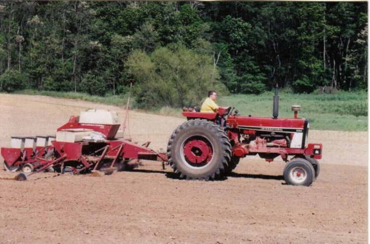 A farmer using his tractor to plant crops
