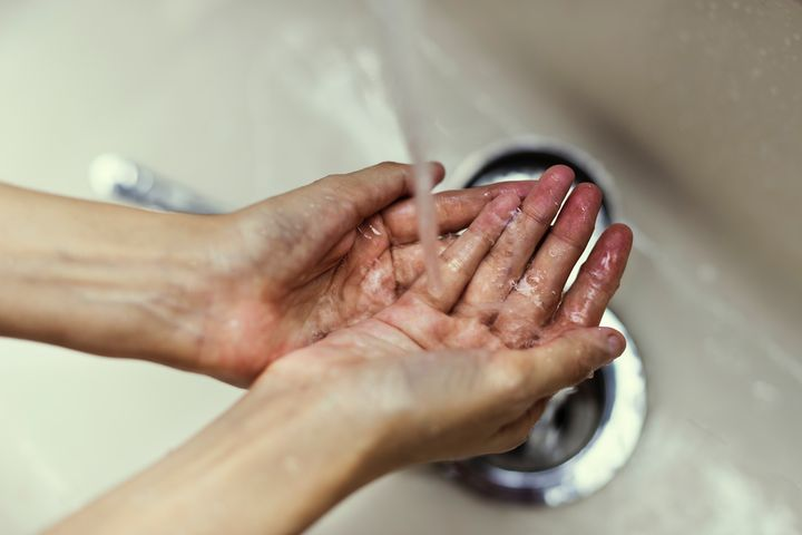 Hands under running water in sink.