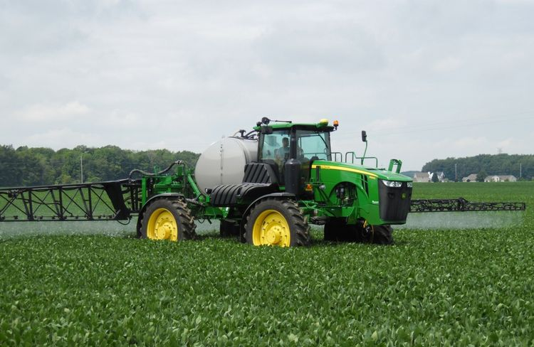 A tractor spraying a field.