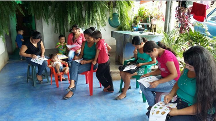 Women and children sit together for a nutrition education session