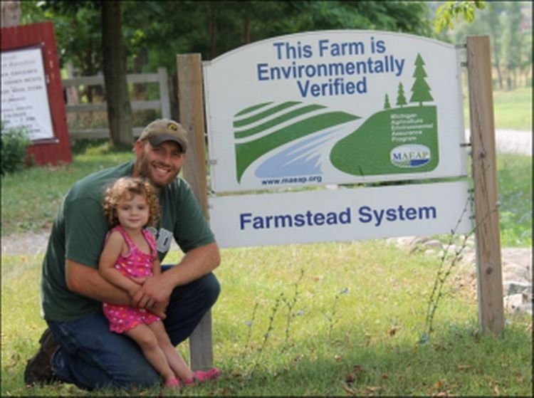 Ben Tirrell in front of the MAEAP sign at Tirrell  Farmstead Specialties. Photo courtesy of MAEAP.org and Tirrell Farms.