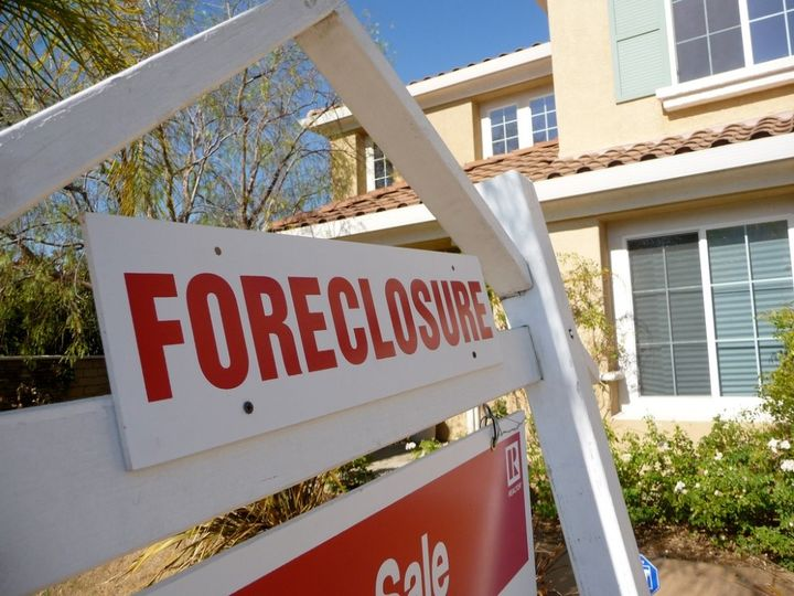 a sign in front of a house stating foreclosure