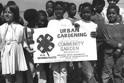 Youth holding up a 4-H sign about their community garden project in Detroit.