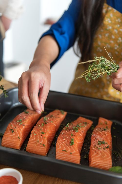 Salmon with rosemary being prepared by a woman in an apron.
