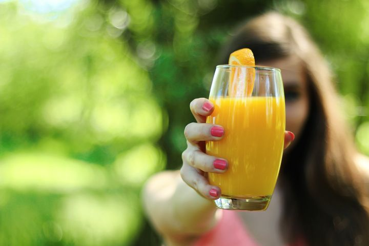 Woman holding a glass of juice.