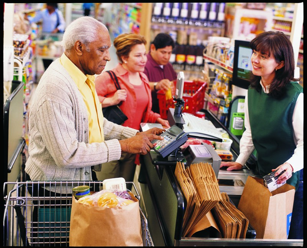 A man using the payment keypad at a grocery store checkout while a clerk bags the groceries.