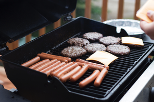 Hot dogs and burgers cooking on a grill.