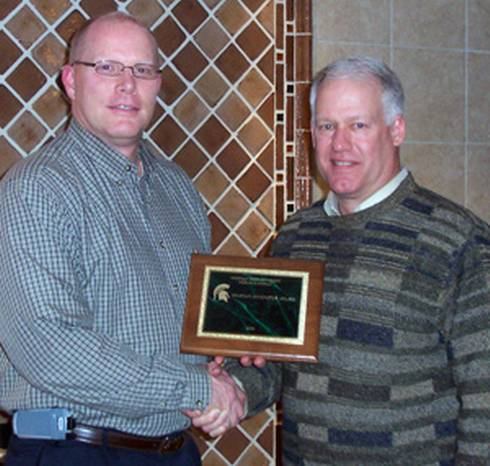 Doug Carmichael (right), manager of the Lake City Experiment Station, accepts the 2009 Spartan Innovator Award from Ben Darling.
