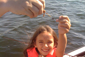 A young angler shows off a pumpkinseed fish caught on the Huron River. | Michigan Sea Grant