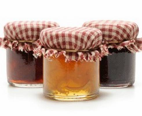 Three jars of jam with lid covered with fabric.