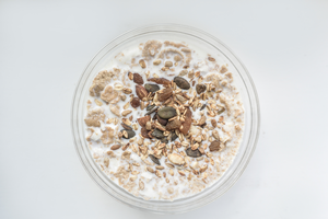 Oatmeal mixed with yogurt and seeds in a jar.