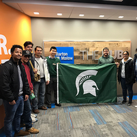 Image of students from the SPDC Construction Management Program and College of Engineering's Civil Engineering Program holding an MSU Spartan flag in Barton Malow.