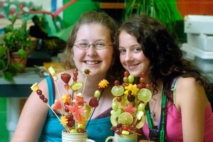 Girls making fruit center pieces