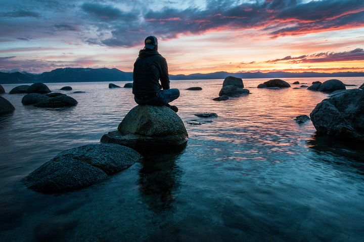 Man sitting on a rock staring at the sunrise.