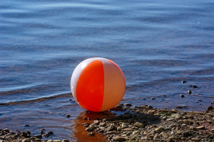 A beach ball on a rocky shore.