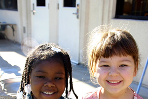 Two preschool aged children sitting together and smiling.