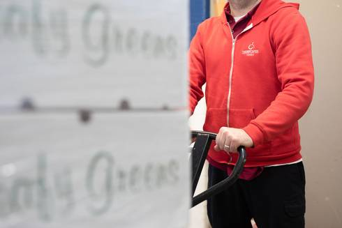 Cherry Capital Foods employee pushes a pallet jack covered with boxes of leafy greens.
