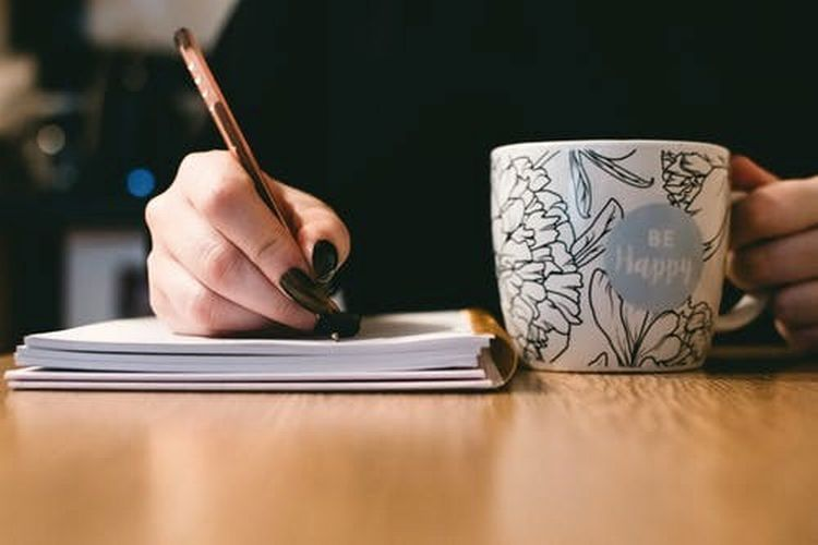 Closeup of person's hands as they write in a notebook, with a pencil in one hand and a coffee mug in the other.